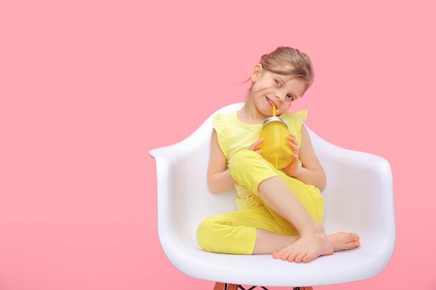 Мечтает молодая девушка с лимонадом на розовом Premium Фотографии