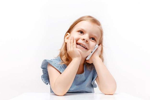 Мобильный телефон счастливого ребёнка говоря изолированный на белизне. крупный план Premium Фотографии