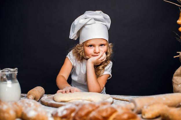 Маленькая девочка замешивает тесто за столом Premium Фотографии