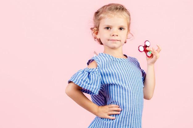 Девушка в синей раздетой рубашке играет красную прядильщику в руке Premium Фотографии