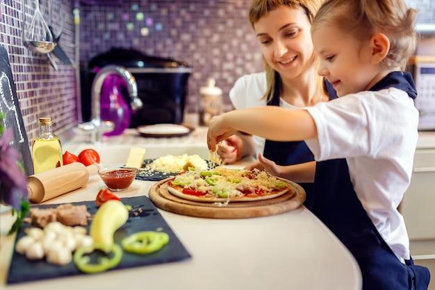小さな女の子と料理の女性 Premium写真