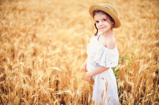 秋の麦畑で幸せな子。白いドレスと麦わら帽子で美しい少女は、遊んで、収穫を楽しんでいます Premium写真