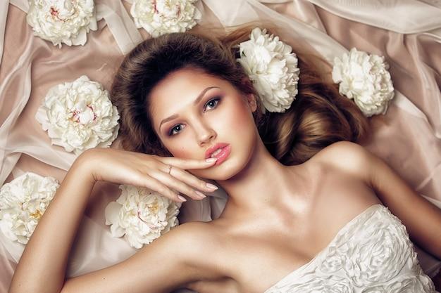 花で横になっているファッショナブルなドレスで官能的な女性 Premium写真