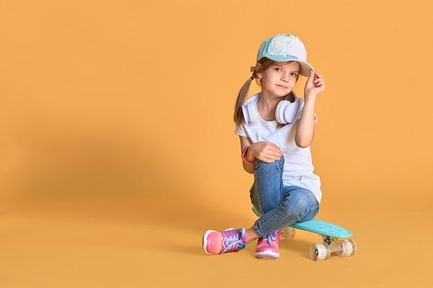 黄色の上のスケートボードとカジュアルでスタイリッシュな小さな女の子子供女の子。 Premium写真