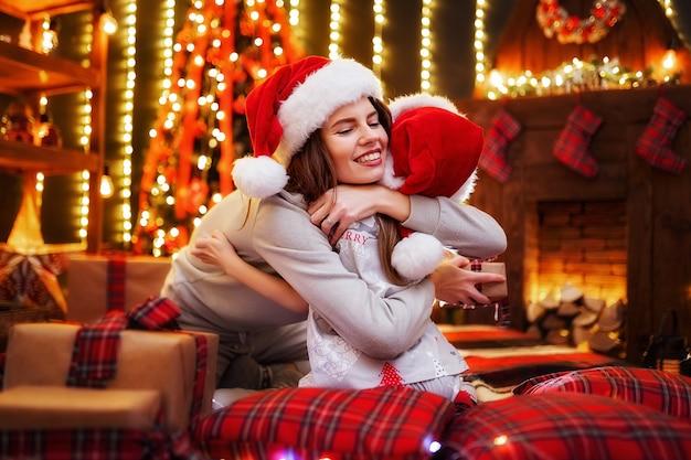 陽気なママと贈り物を交換する彼女のかわいい娘の女の子。屋内の木の近くで楽しんでいる親と小さな子供たち。クリスマスルームでプレゼントを愛する家族。 Premium写真