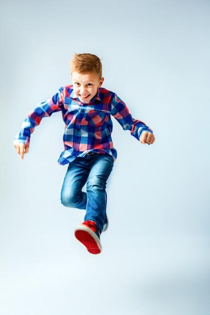 カラフルな格子縞のシャツ、ブルージーンズ、ための半靴で小さな男の子をジャンプします。分離されました。 Premium写真