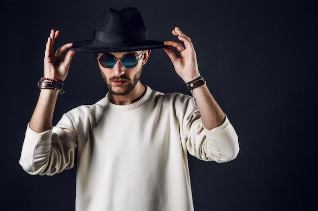 Крутой стильный красавец в темных очках держит шляпу Premium Фотографии