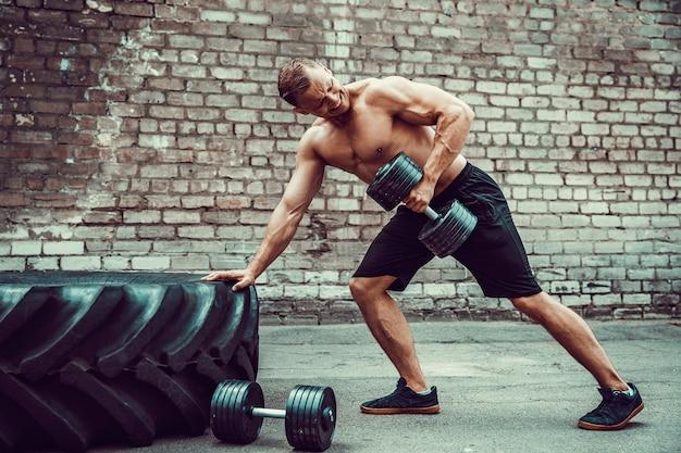 ダンベルでワークアウト運動の男。強さと動機。背中の筋肉の運動 Premium写真