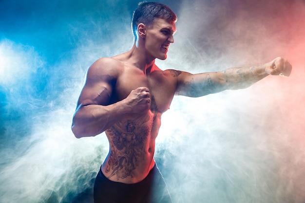 Мускулистый боец, пробивая дым Premium Фотографии
