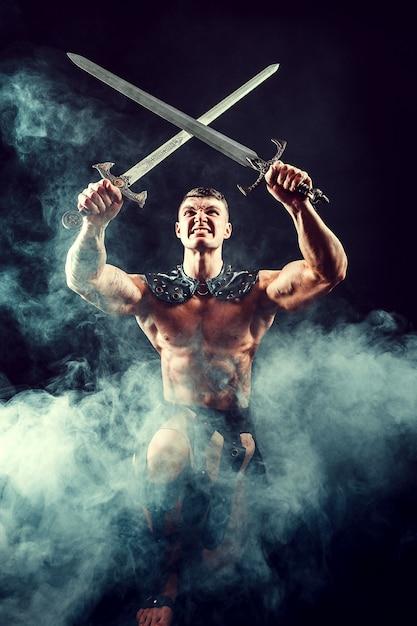 剣で激しくポーズ筋肉の上半身裸の男 Premium写真