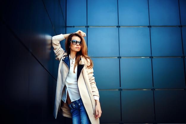 ベージュのコートとブルージーンズの女の子 Premium写真