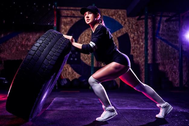 魅力的なフィット女性アスリートは、巨大なタイヤでワークアウト、回転し、ジムで反転します。大きなタイヤで運動フィットの女性 Premium写真