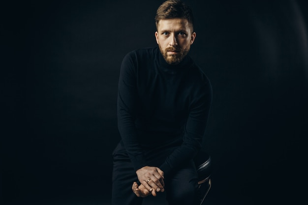 Уверенный в себе мужчина в черном позирует на стуле Premium Фотографии