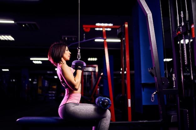 ジム-背面図で、マシンを使用して背中の運動を行う運動の女性 Premium写真