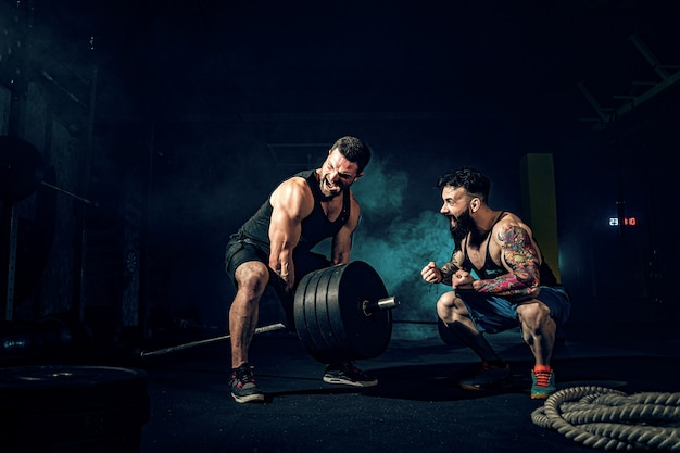 Два мускулистых бородатых татуированных спортсмена тренируются в спортзале Premium Фотографии
