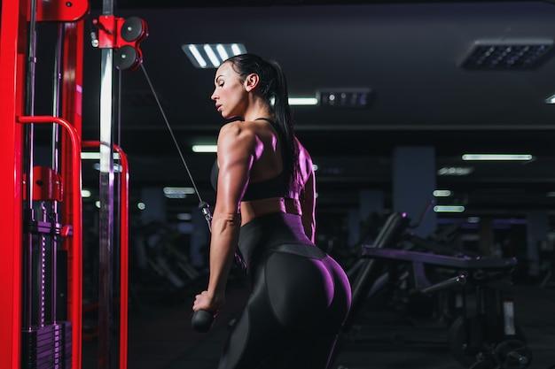 Атлетическая сексуальная женщина делая тренировку используя машину в спортзале - взгляд со стороны Premium Фотографии