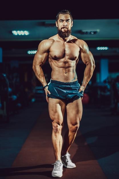 ジムでポーズをとって運動筋肉ボディービルダー男。 Premium写真