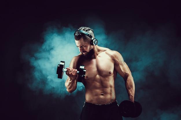 男は煙で暗い背景にスタジオでダンベルで筋肉をトレーニングします。 Premium写真