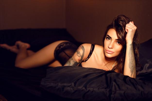 寝室でポーズをとってスタイリッシュな下着を着ているセクシーな女の子の私室写真。 Premium写真