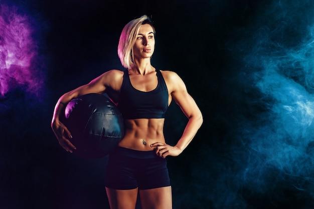 薬のボールでポーズファッショナブルなスポーツウェアでスポーティな金髪女性。煙で暗い壁に筋肉の女性の写真。強さと動機。 Premium写真