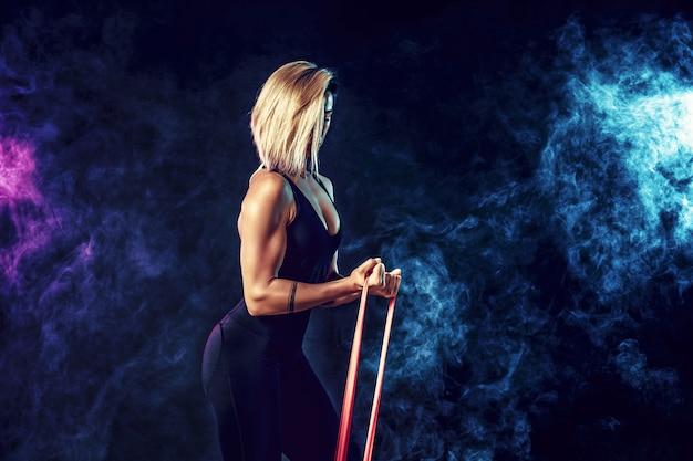 彼女の運動ルーチンで抵抗バンドを使用してスポーツウェアでセクシーな女性。若い女性は煙で黒い壁にフィットネス運動を実行します。分離する Premium写真