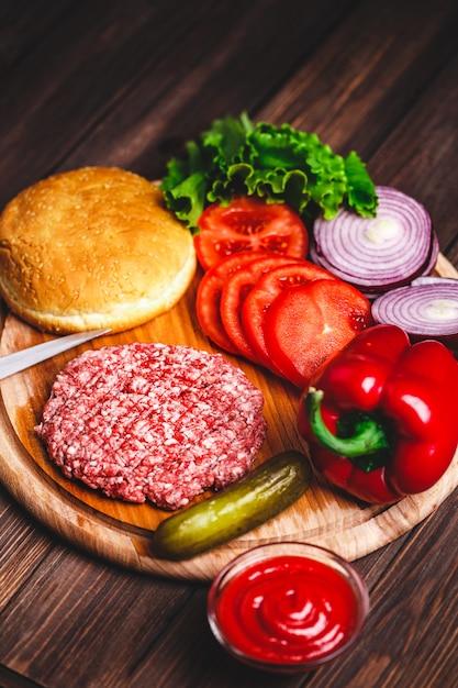 生のひき肉ハンバーガーステーキカツレツ調味料、チーズ Premium写真