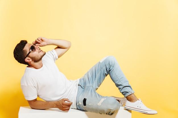 Загорелый красавец лежал на белой коробке Premium Фотографии