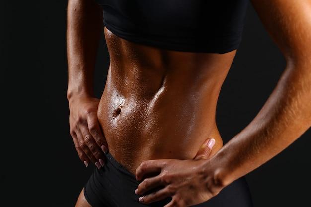 黒のスポーツウェアで大きな腹筋を持つスポーティなセクシーな女の子。 Premium写真