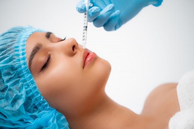 美容師は、美容院で女性の顔の皮膚のしわを引き締め、滑らかにするために、若返りの顔の注入手順を行います。美容スキンケア Premium写真