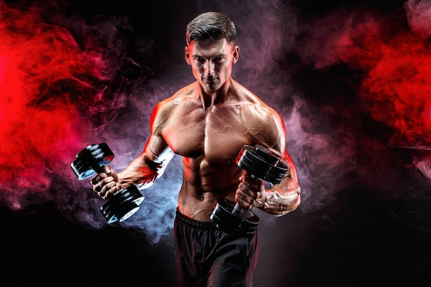 Концентрированный мускулистый мужчина делает упражнения с гантелями Premium Фотографии
