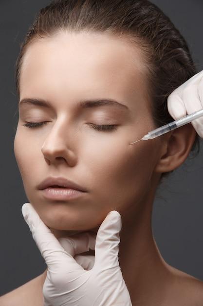 化粧品の注入を得る若い女性の肖像画 Premium写真