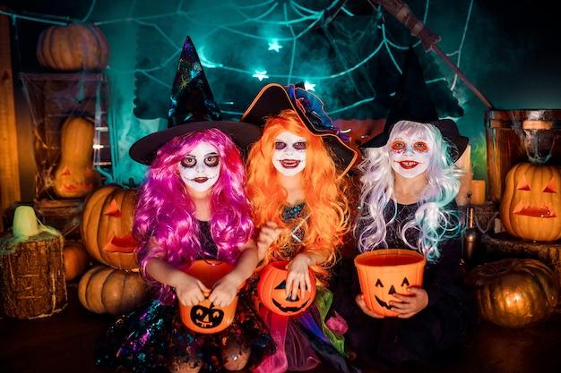 Три милые смешные сестры празднуют праздник. веселые дети в карнавальных костюмах готовятся к хэллоуину. Premium Фотографии