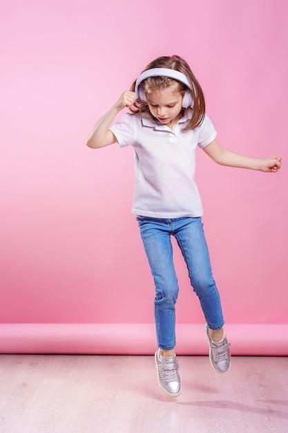 ピンクの壁にヘッドフォンで音楽を聴いている女の子。踊る少女。音楽に合わせて踊る幸せな小さな女の子。幸せなダンス音楽を楽しんでいるかわいい子。 Premium写真
