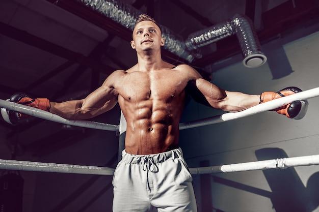 次の試合のトレーニング中にリングの隅にあるロープで休む筋肉のプロキックボクサー Premium写真
