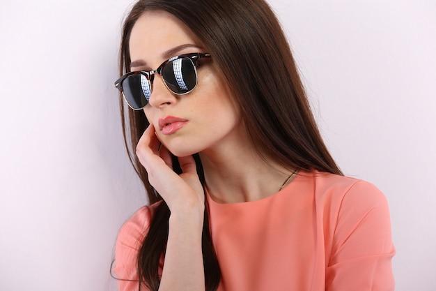 サングラスと長い髪のポーズの美しいブルネットの女性 Premium写真