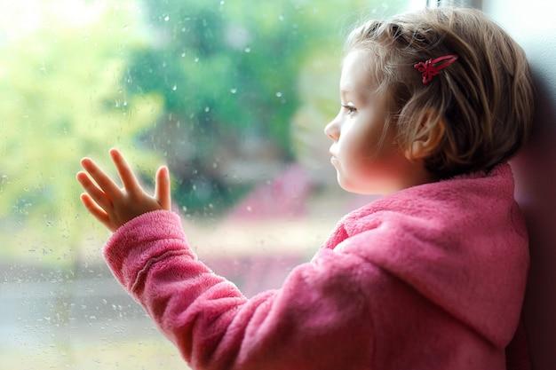 Милая маленькая девочка с хвостиком в розовом халате Premium Фотографии