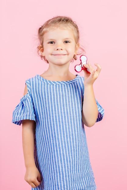 Девушка в синей раздетой рубашке играет красную прядильщицу в руке Premium Фотографии