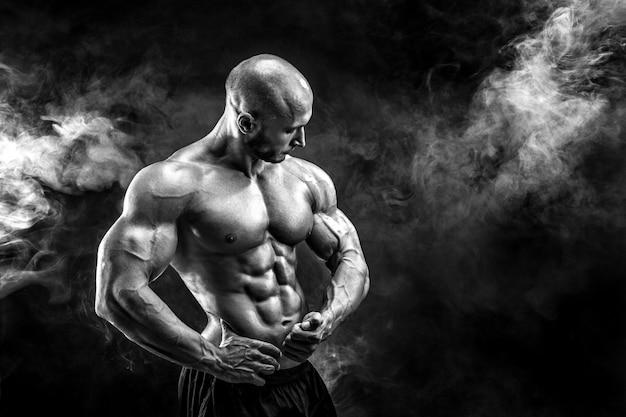 強力なボディービルダーポーズと筋肉を見せて Premium写真