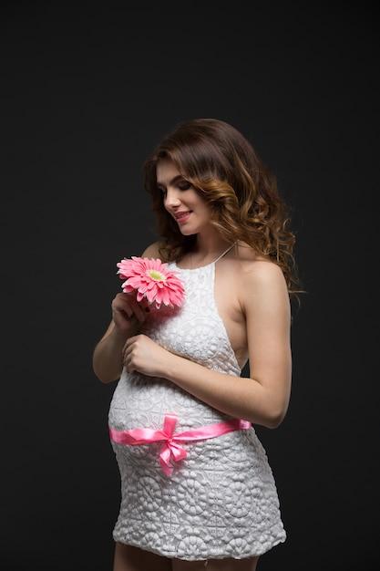 Беременная красивая брюнетка в белом платье с идеальным макияжем и прической, держа розовый цветок Premium Фотографии