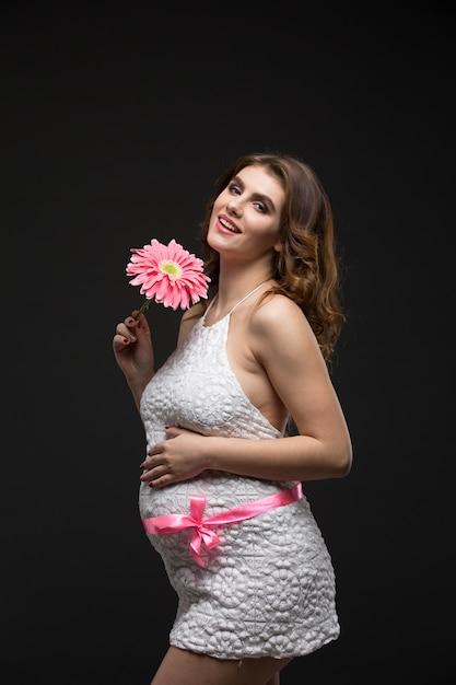 ピンクの花を保持している完璧なメイクや髪型と白いドレスに妊娠中の美しいブルネットの女性 Premium写真