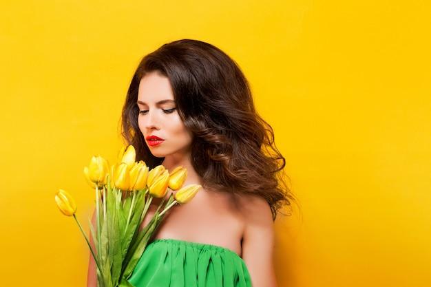 Портрет привлекательная брюнетка в зеленом платье с красивыми цветами Premium Фотографии