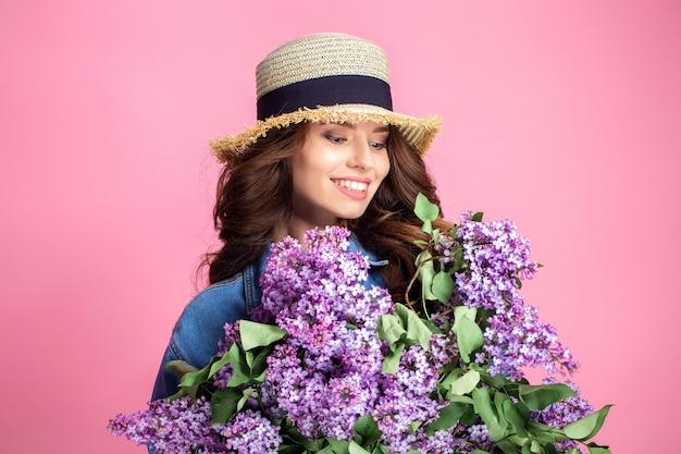 Счастливая улыбающаяся женщина в соломенной шляпе позирует с букетом цветов сирени Premium Фотографии