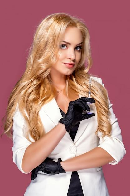 注射器を持って白いジャケットを着ている女性 Premium写真
