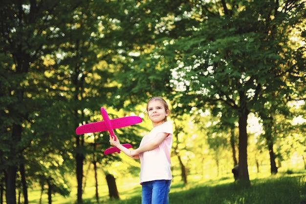 小さな女の子が公園で空中におもちゃの飛行機を起動します Premium写真