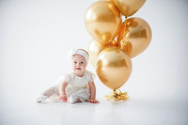 黄金の風船の束と座っている女の赤ちゃん Premium写真