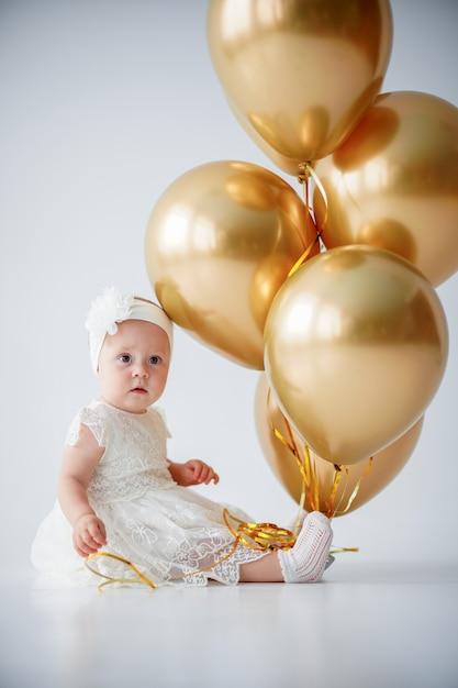 Девочка сидит с букетом золотых шаров Premium Фотографии