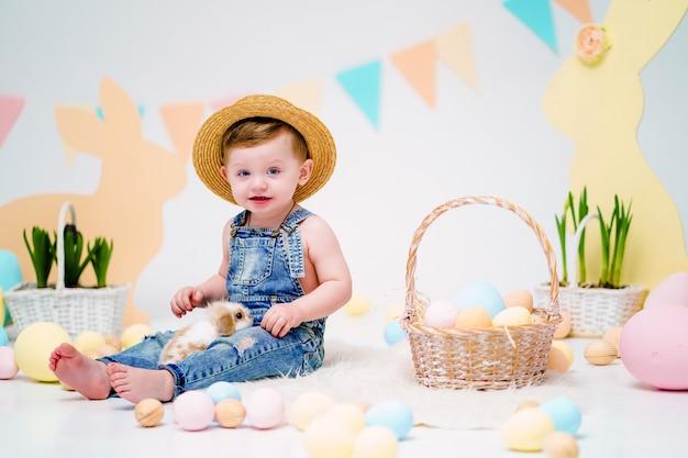 Счастливый маленький мальчик держит милый пушистый кролик возле крашеные пасхальные яйца Premium Фотографии