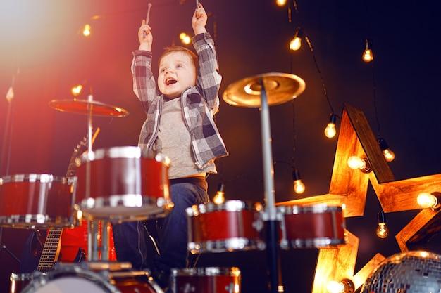 Маленький мальчик играет на барабанах на сцене Premium Фотографии
