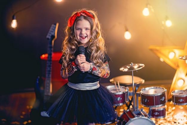 Маленькая красивая девушка поет в студии звукозаписи Premium Фотографии
