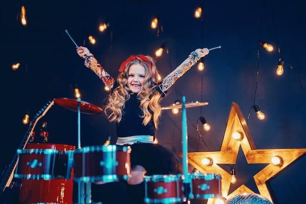 Красивая девушка играет на барабанах Premium Фотографии
